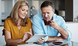 woman and man sit at a table and look at a tablet and papers together