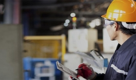 man in hard hat and clipboard looks at factory setting