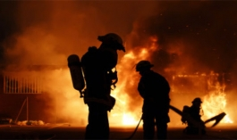 fire fighters silhouettes can be seen in front of a fire
