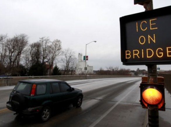 """a car drives past a sign that says """"ice on bridge"""""""