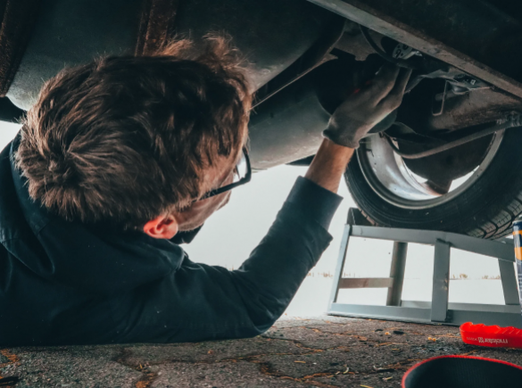 man working on repairing underside of vehicle