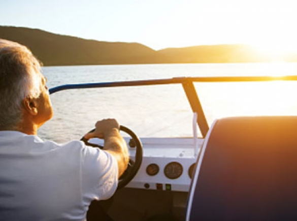 Man driving a boat with sunset