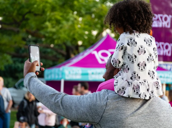 father holds daughter on shoulders at an event and takes a selfie