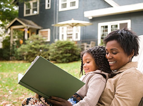 Mother and daughter reading in backyard