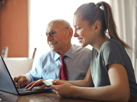 a young woman helps an elderly man with payment on a computer