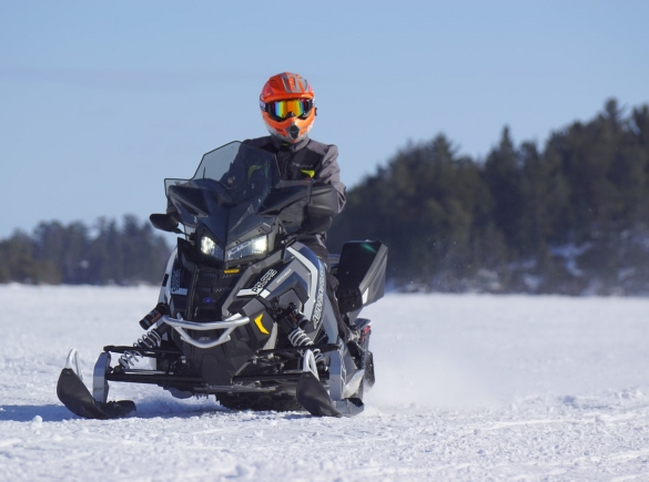 Man on snowmobile with forest in background