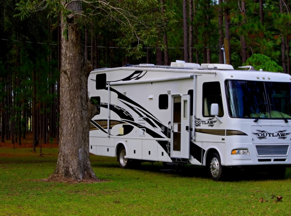 An RV parked in a forest campground