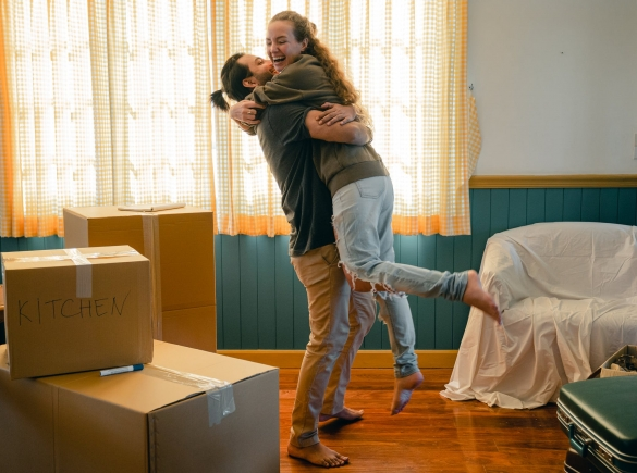 Photo of happy couple hugging, next to moving boxes