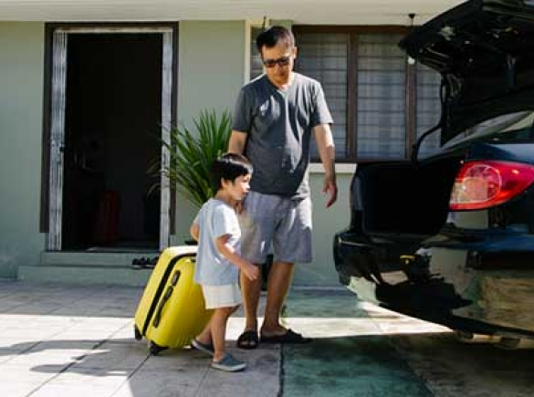 father and son loading car with suitcase