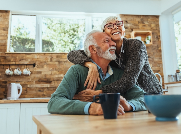 An elderly couple embrace in their kitchen.