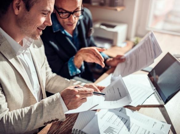 Two men reviewing insurance paperwork.