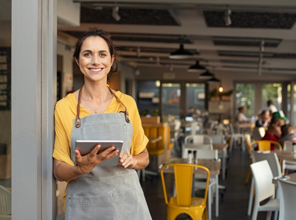 A successful business owner welcomes customers into her shop with a smile.