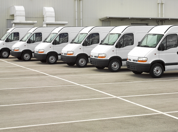A fleet of white work vans parked in a lot.