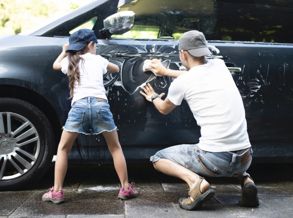 A father and daughter, both wearing backward baseball caps, bond by washing their car.
